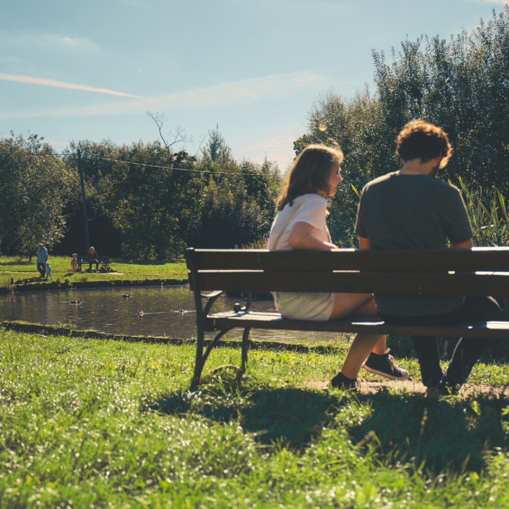 Outdoors, two people sat on bench looking into view on mother's day 2020